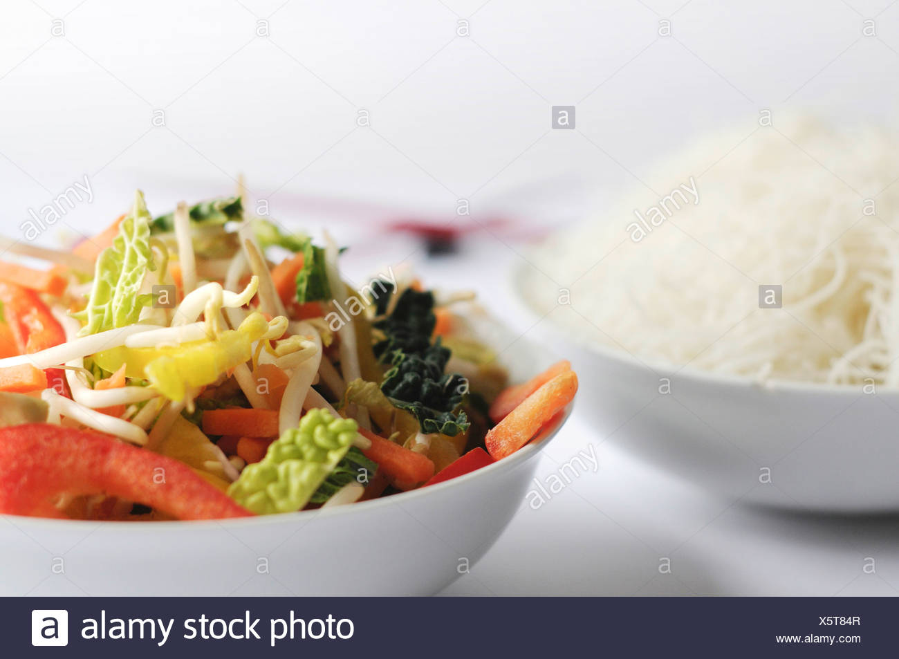 Mixed vegetables and chopsticks and rice noodles - Stock Image