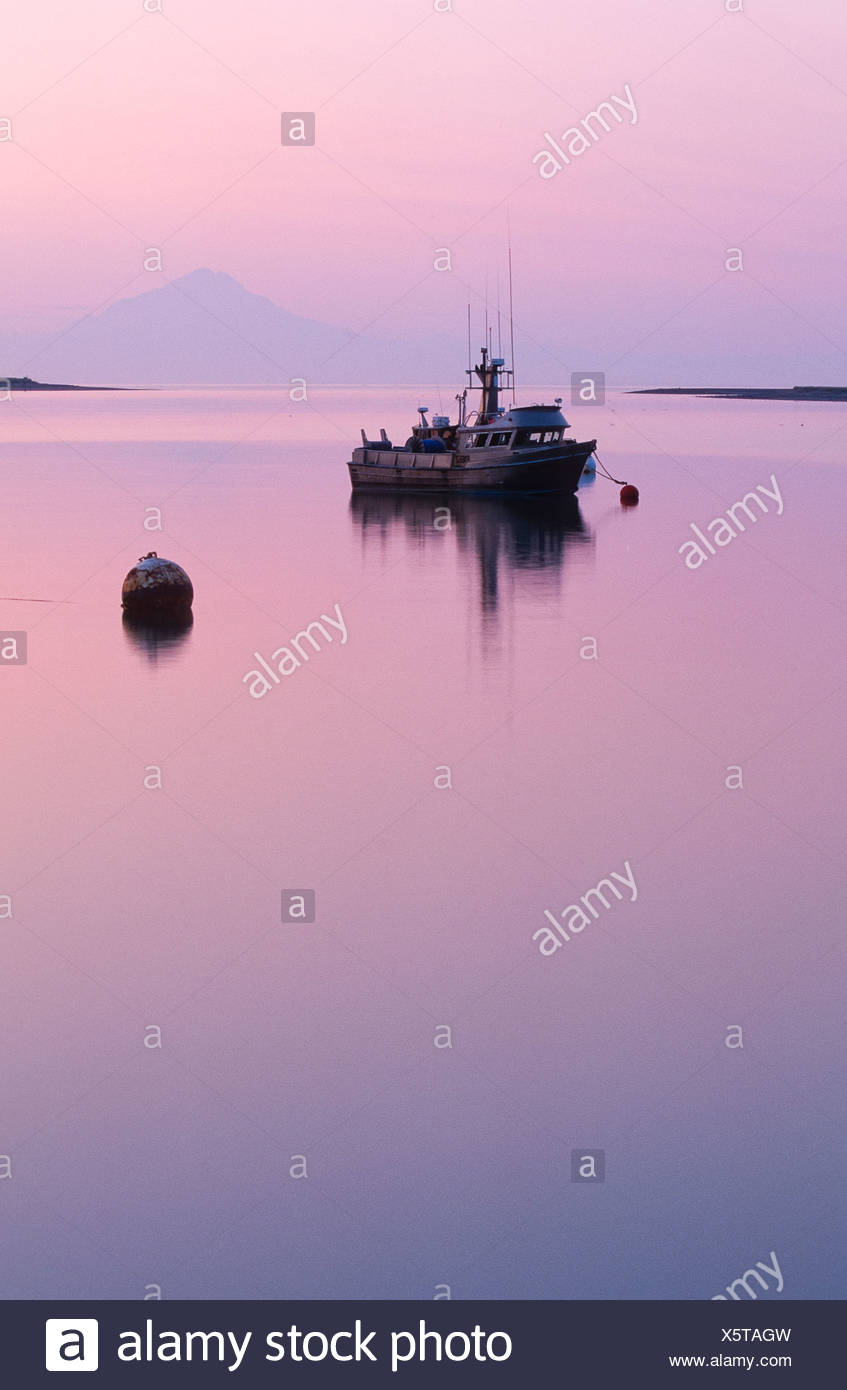Alaska. Kenai Peninsula. Sunset over Redoubt Mt. Volcano across Cook Inlet. Kenai River salmon commercial fishing boat. - Stock Image