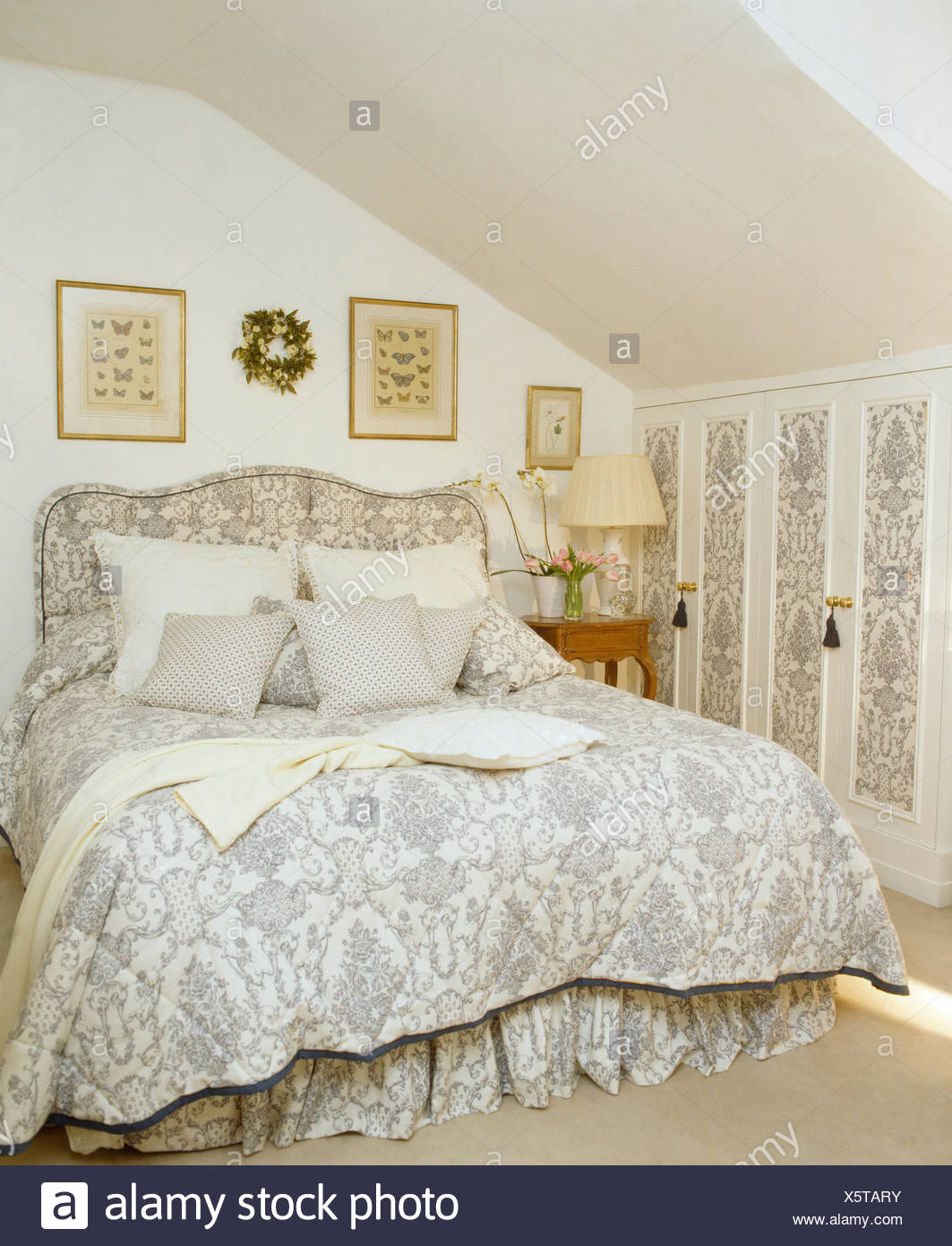 Pale Grey White Quilt And Upholstered Headboard On Bed In Attic Bedroom With Wallpaper Panels On Cupboard Door Stock Photo Alamy