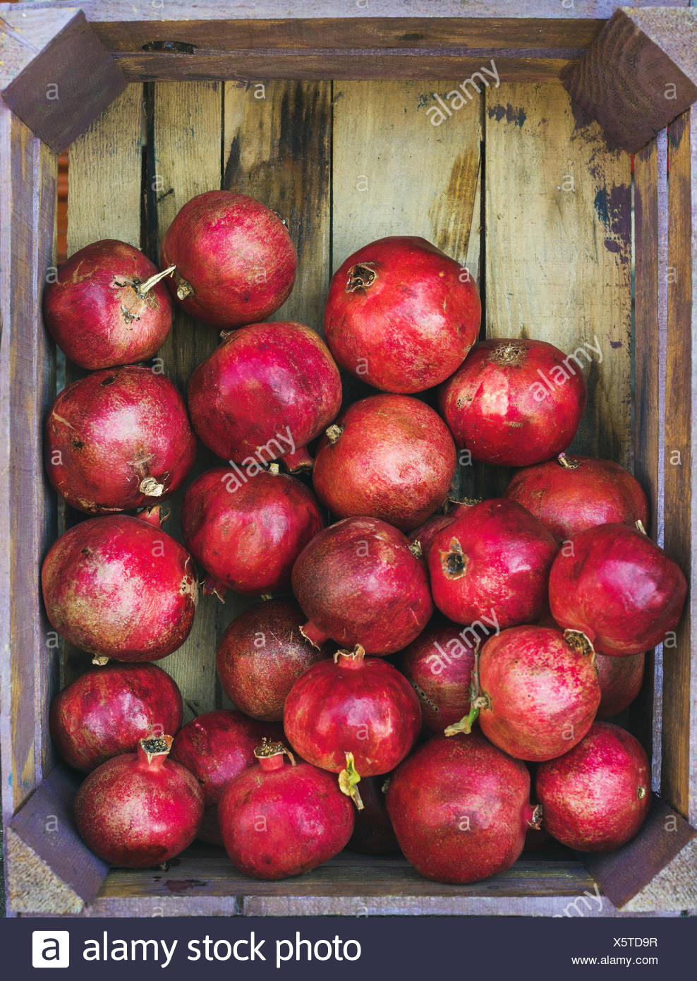 Turkish ripe red pomegranates in rustic wooden box, top view, copy space, vertical composition Stock Photo