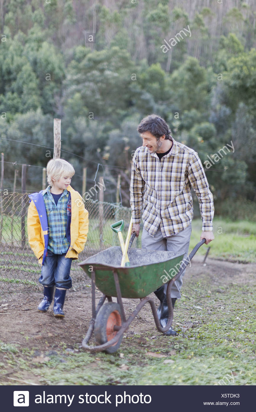 Father and son pushing wheelbarrow - Stock Image