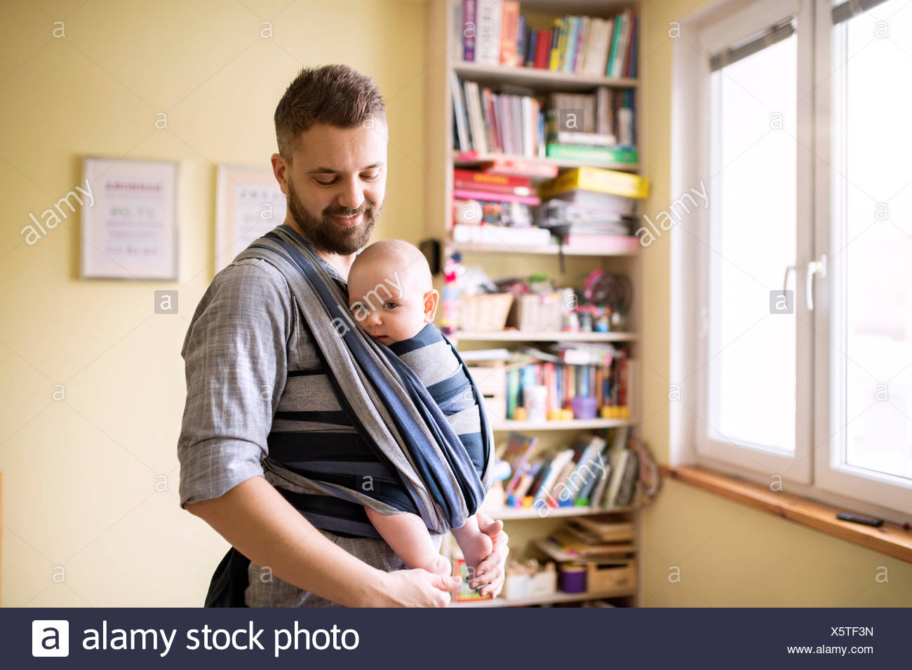Father with baby son in sling at home - Stock Image