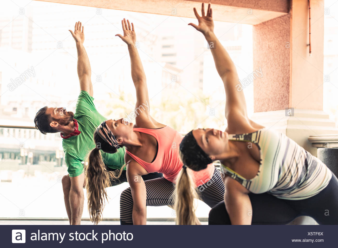 Group of young adults doing yoga - Stock Image