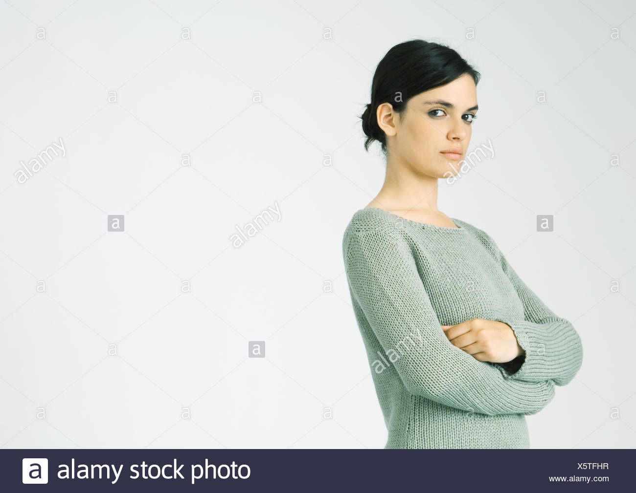 Young woman standing with arms crossed, looking at camera - Stock Image