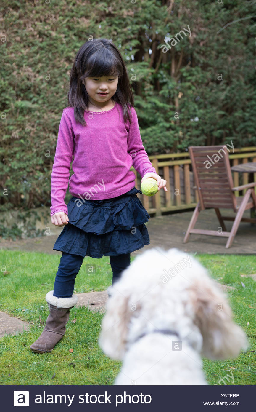 Girl playing ball with her pet dog in the garden - Stock Image