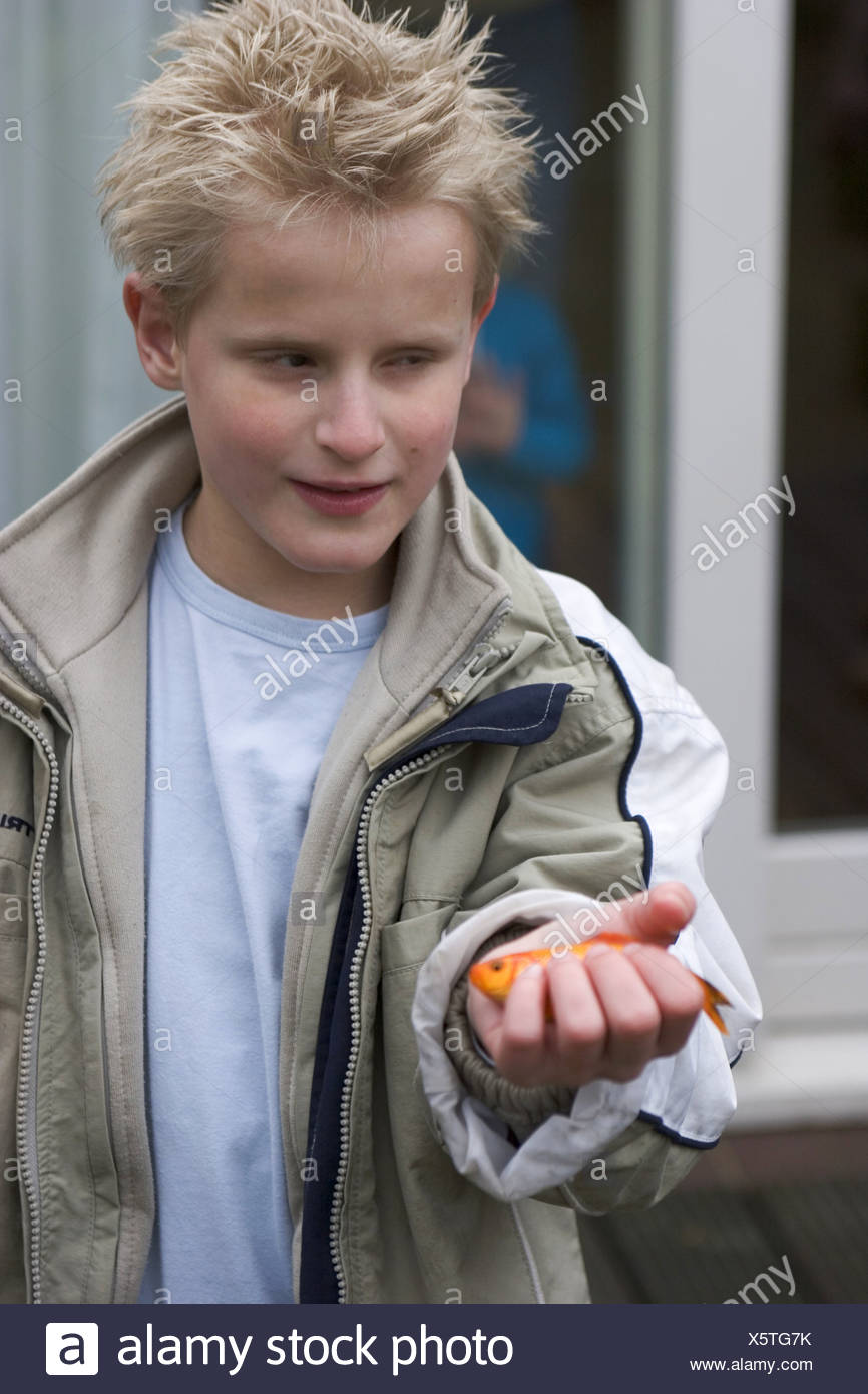 Blind boy playing with fish - Stock Image