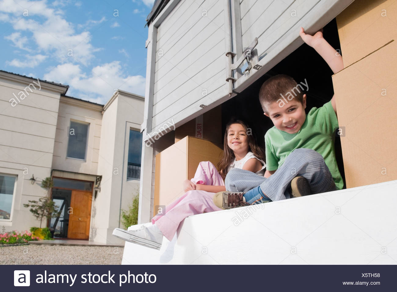 Portrait of a boy sitting with his sister in a pick-up truck and smiling - Stock Image