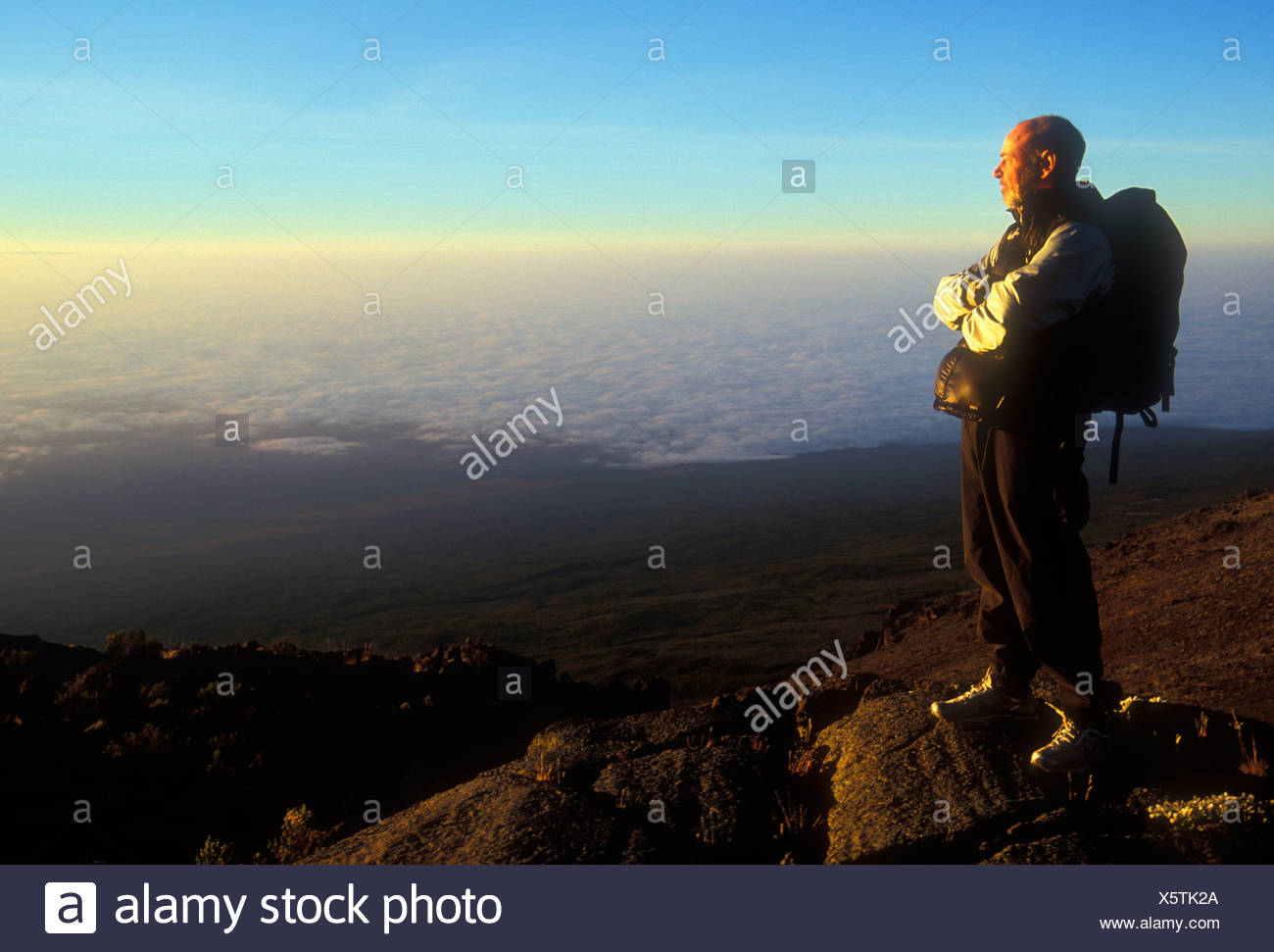A man stands alone at sunrise as he looks down to the Tanzanian plains below Mount Kilimanjaro. John is attempting to climb to t - Stock Image