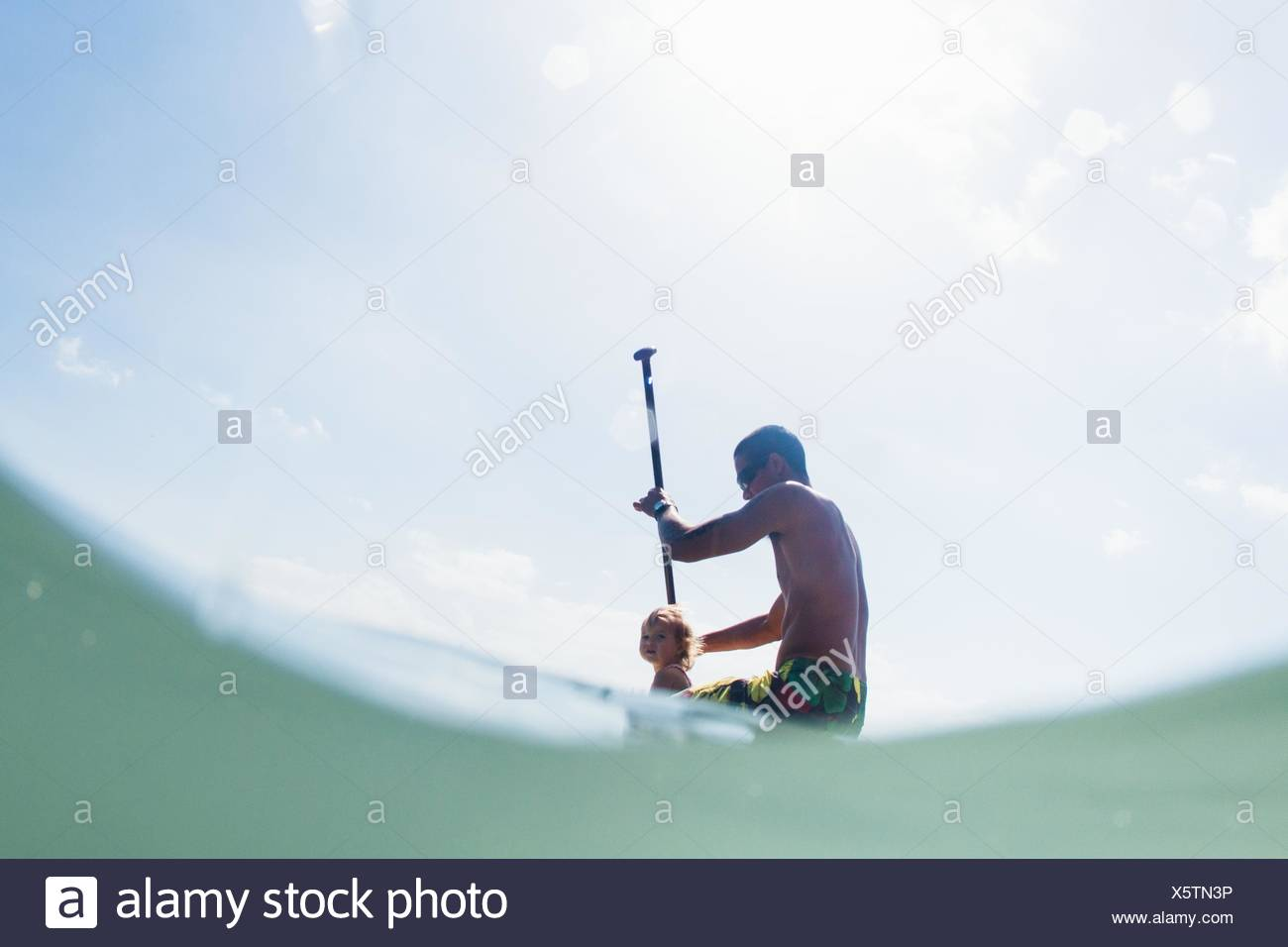 Low angle view of young man and toddler daughter paddleboarding Stock Photo