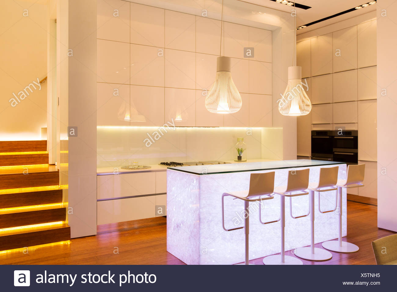 Bar stools and lighting in modern kitchen - Stock Image