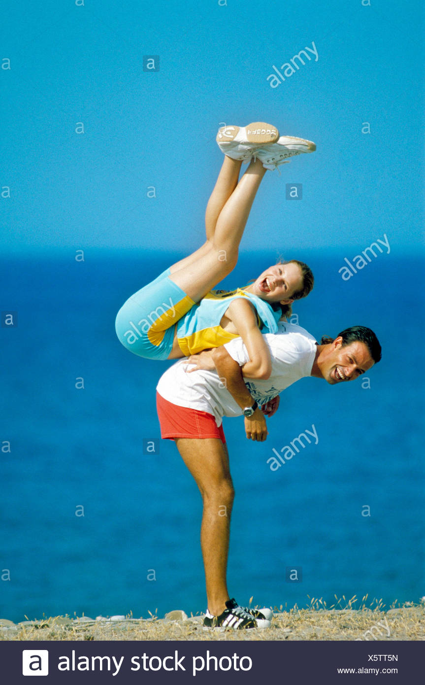 Couple on hill by sea Male lifting female up in air on his back linked arms Female dark blonde hair tied up wearing light blue - Stock Image