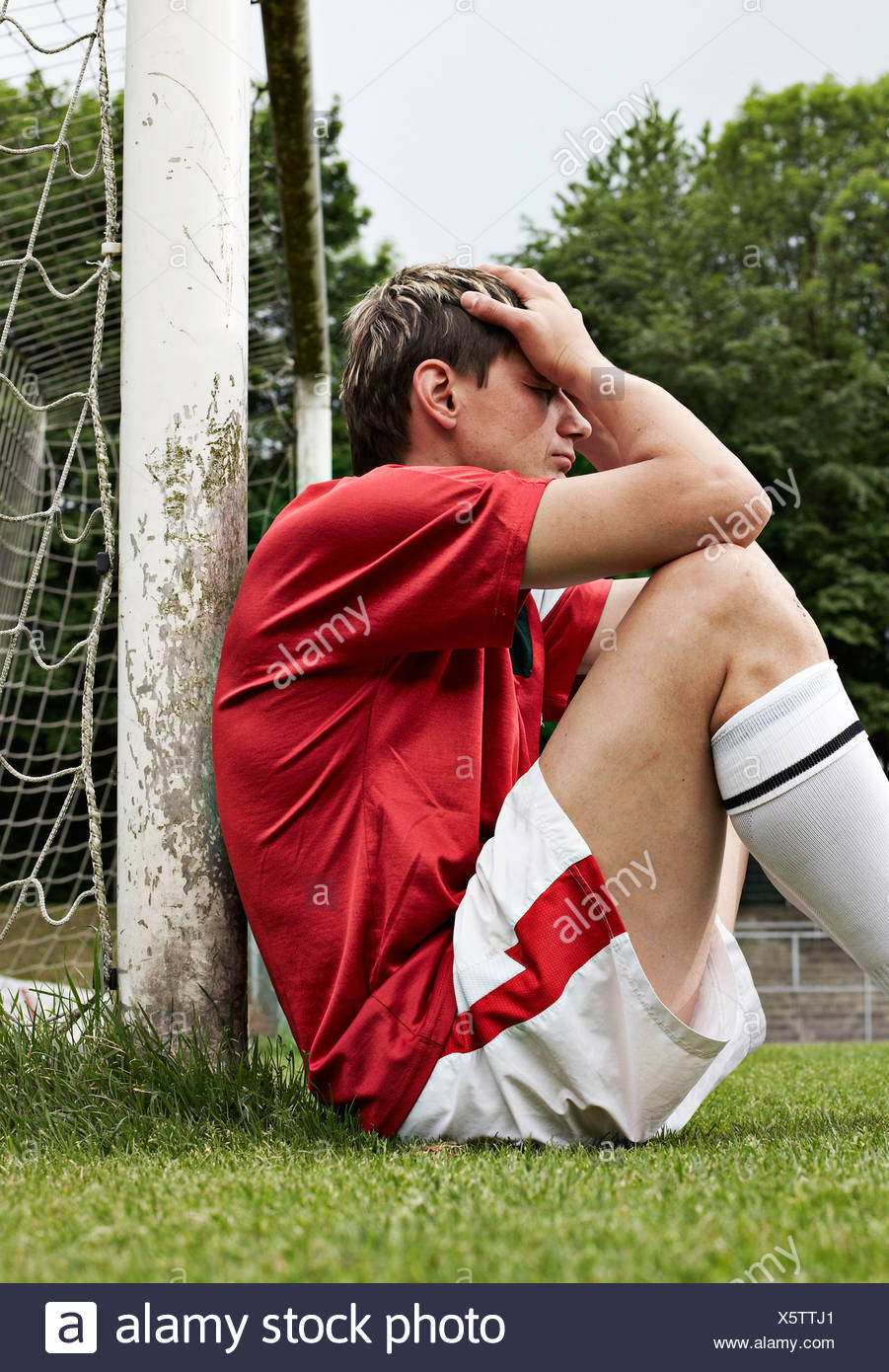 Frustrated soccer player on field - Stock Image
