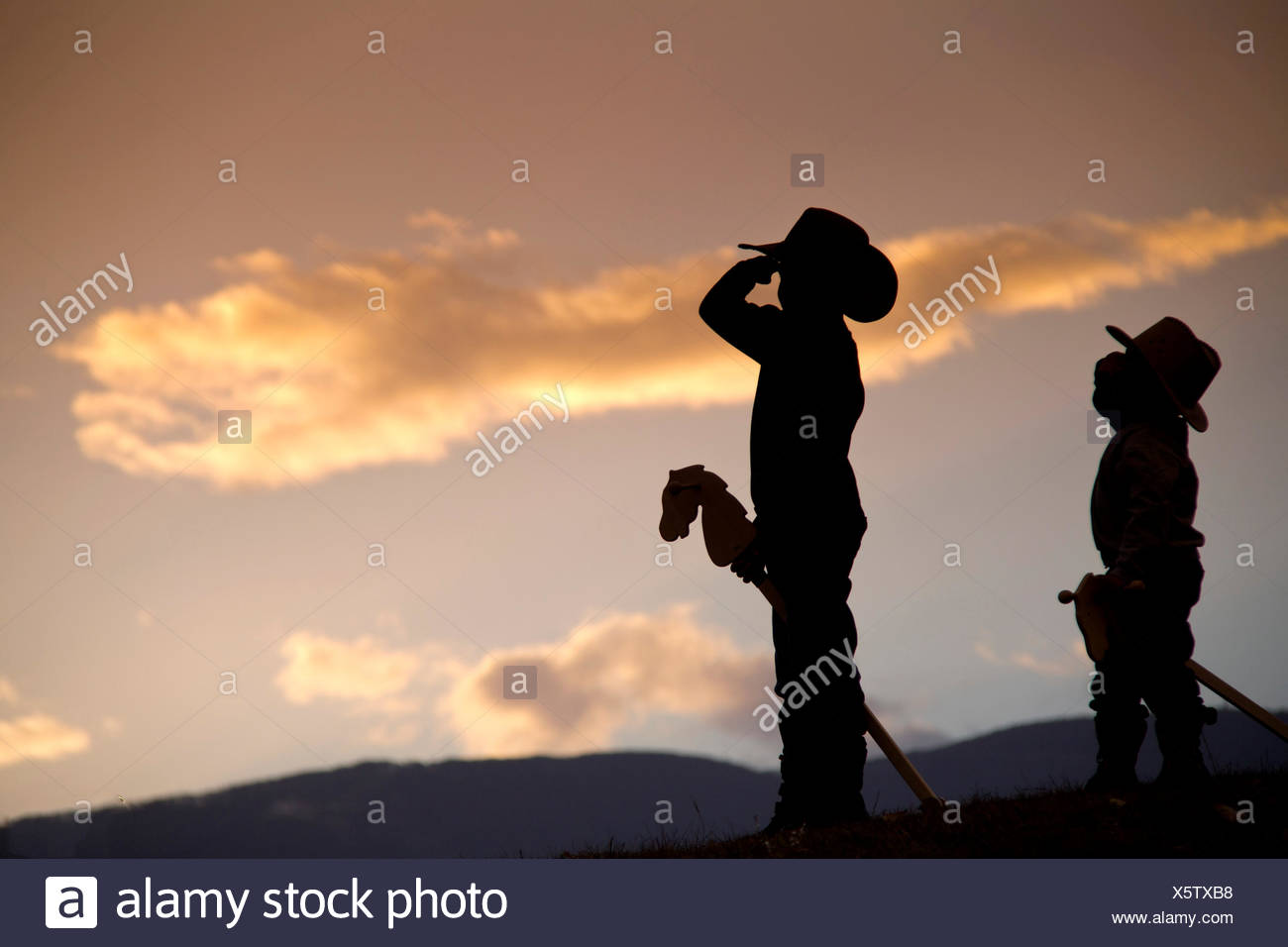 Silhouette of two boys with hobby horses pretending to be cowboys saluting with pride - Stock Image
