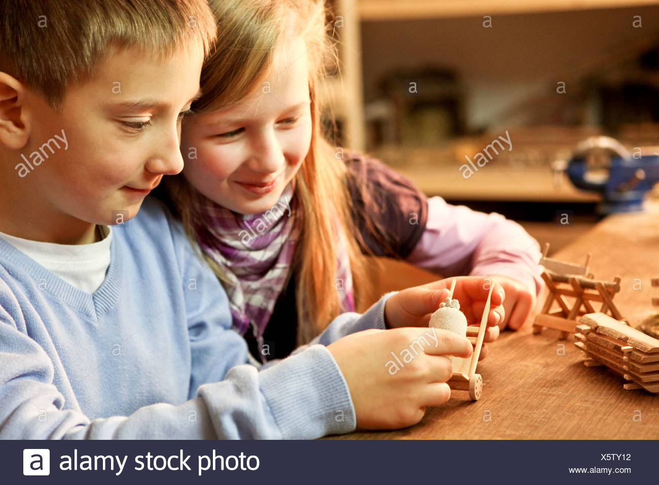 Young boy and girl making wooden craft together - Stock Image
