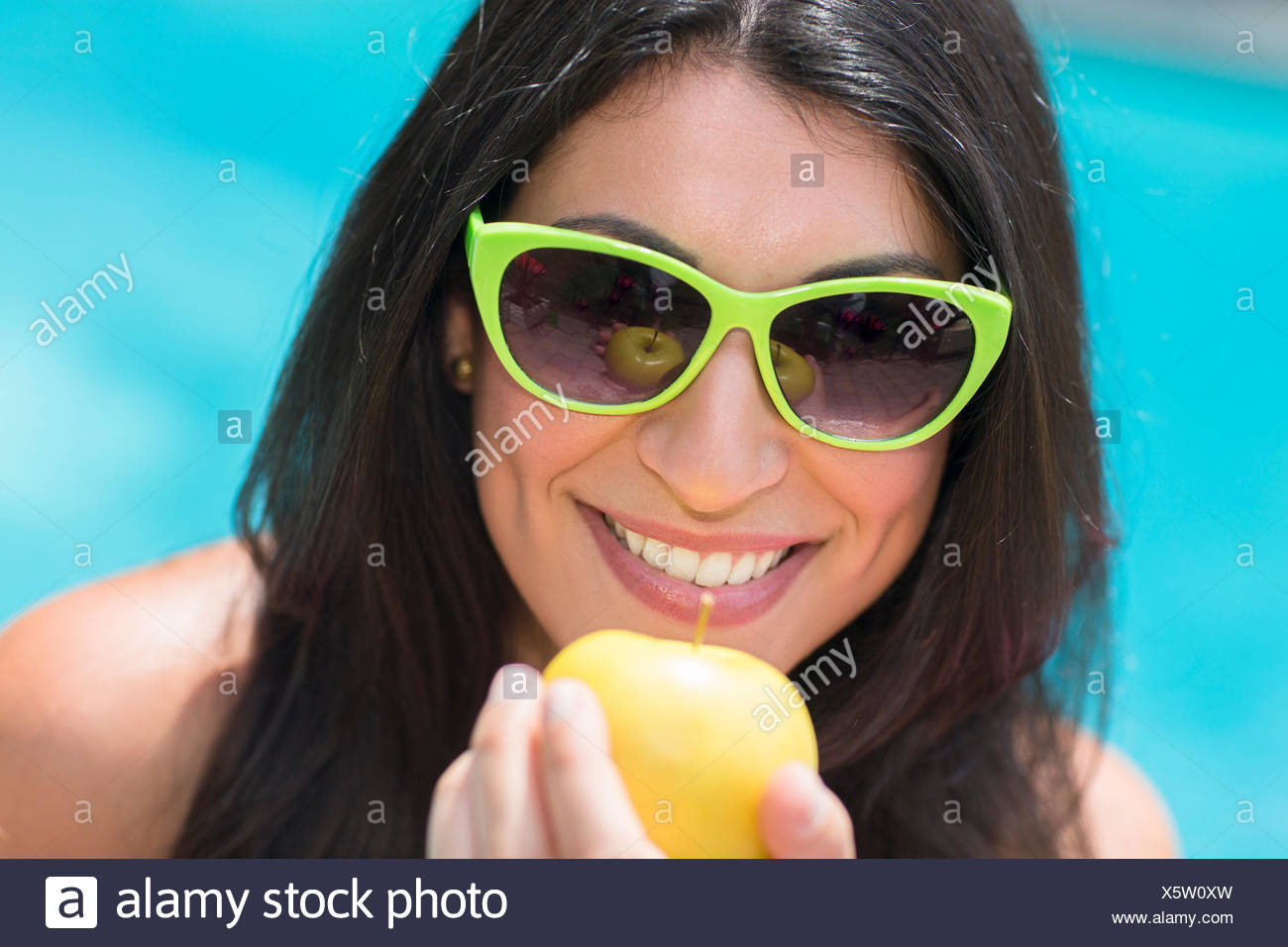 Portrait of young woman by pool holding up apple - Stock Image