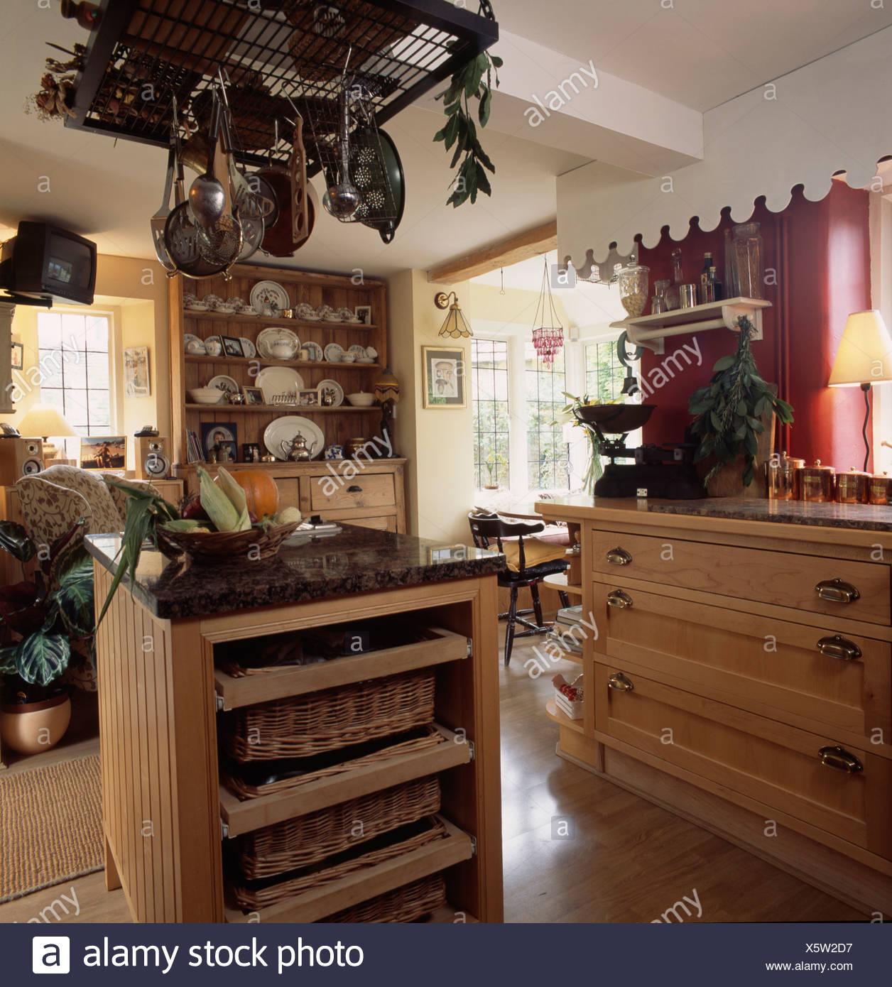Pans on storage rack above island unit with wicker storage ...
