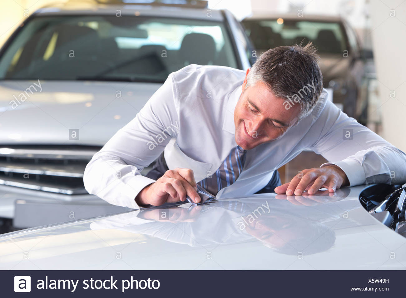 Salesman wiping automobile hood with tie in car dealership showroom - Stock Image