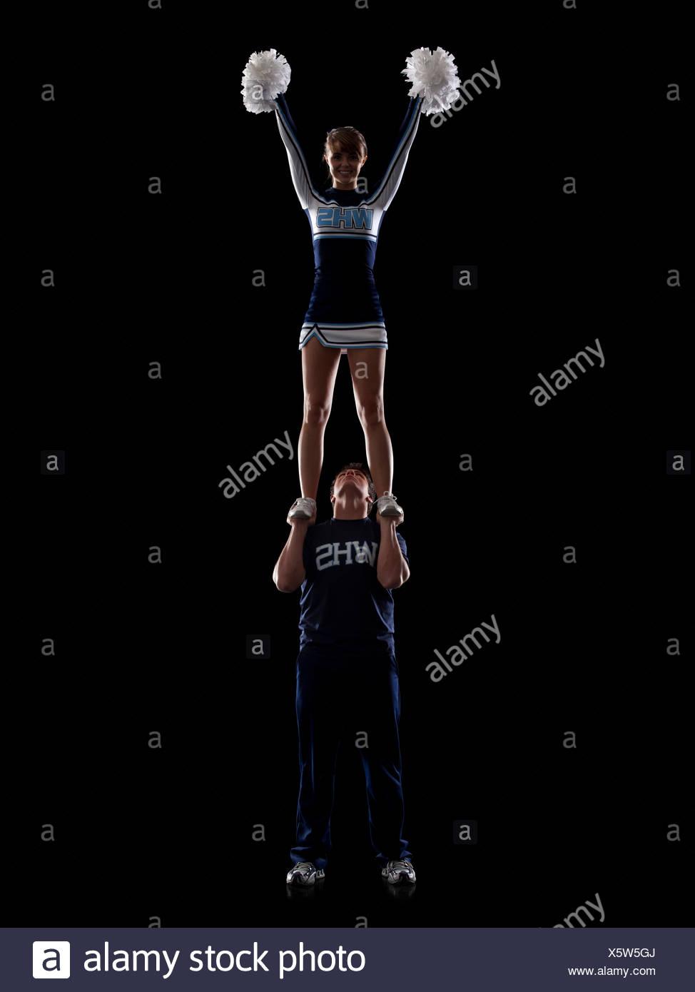 Teenage sportsman(16-17) holding aloft teenage cheerleader girl (16-17) - Stock Image