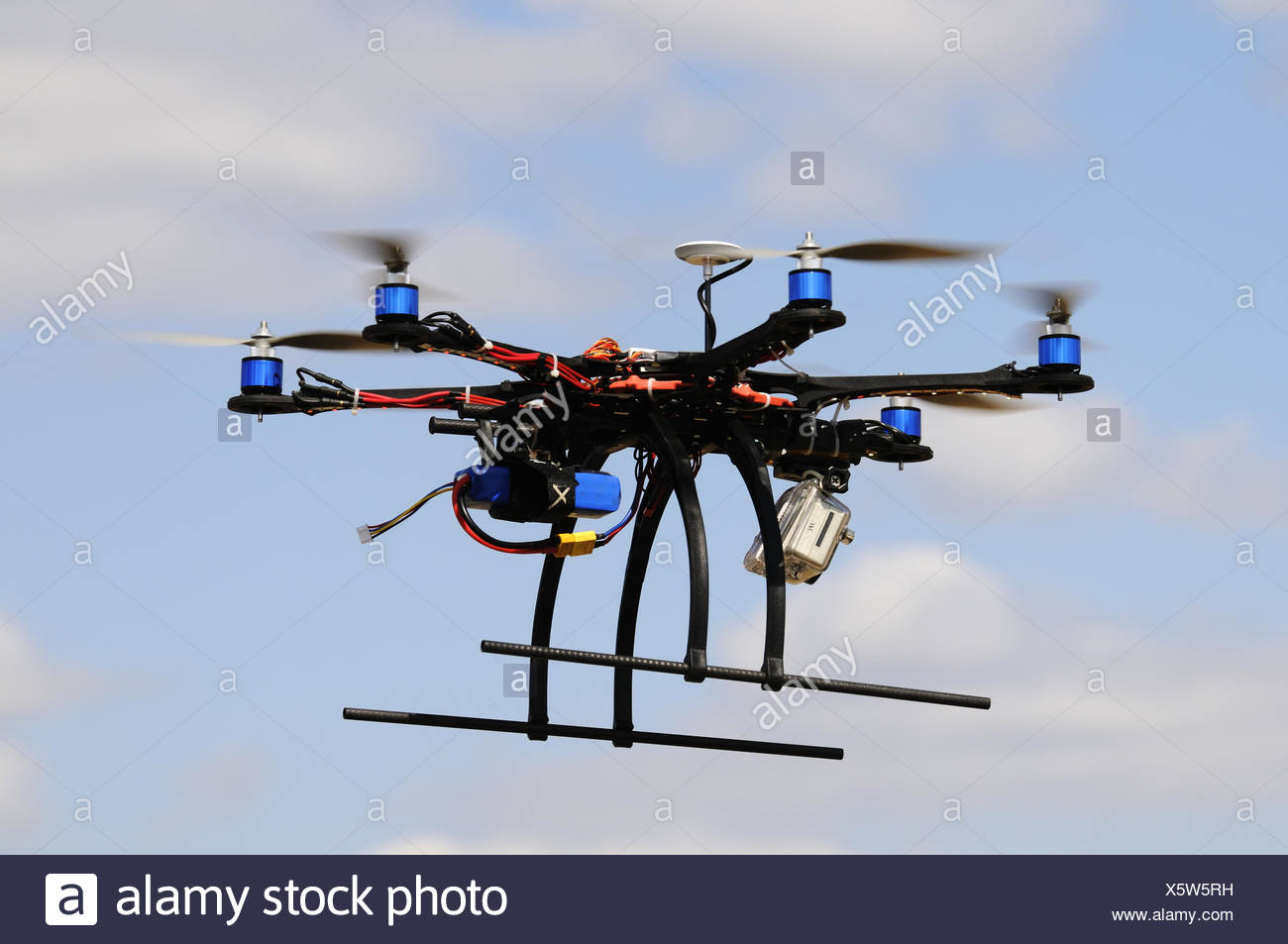 Hexacopter aircraft model in flight over blurry blue sky - Stock Image