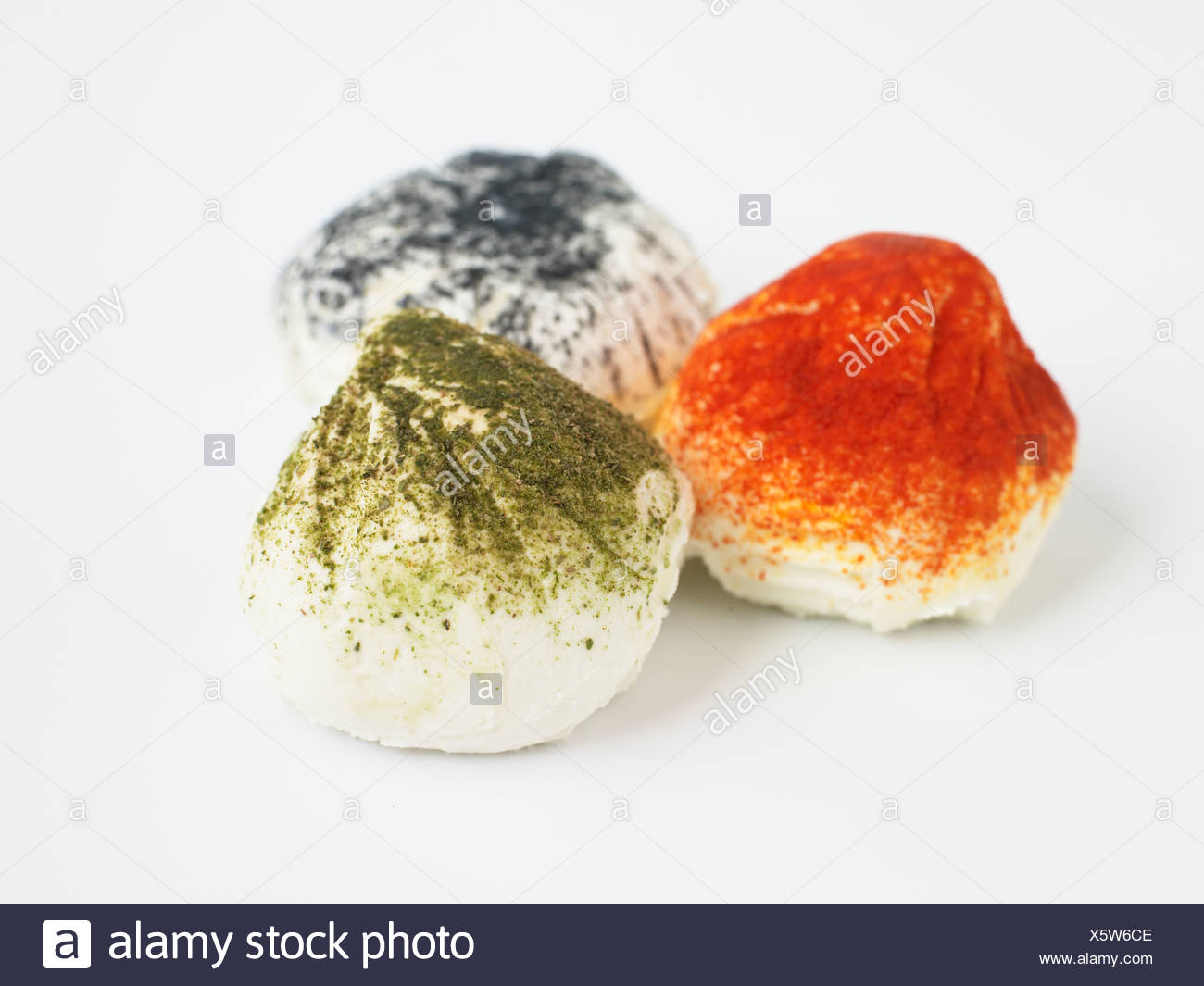 French Figuette goat's cheeses on white background, ash, paprika and tarragon, close-up - Stock Image