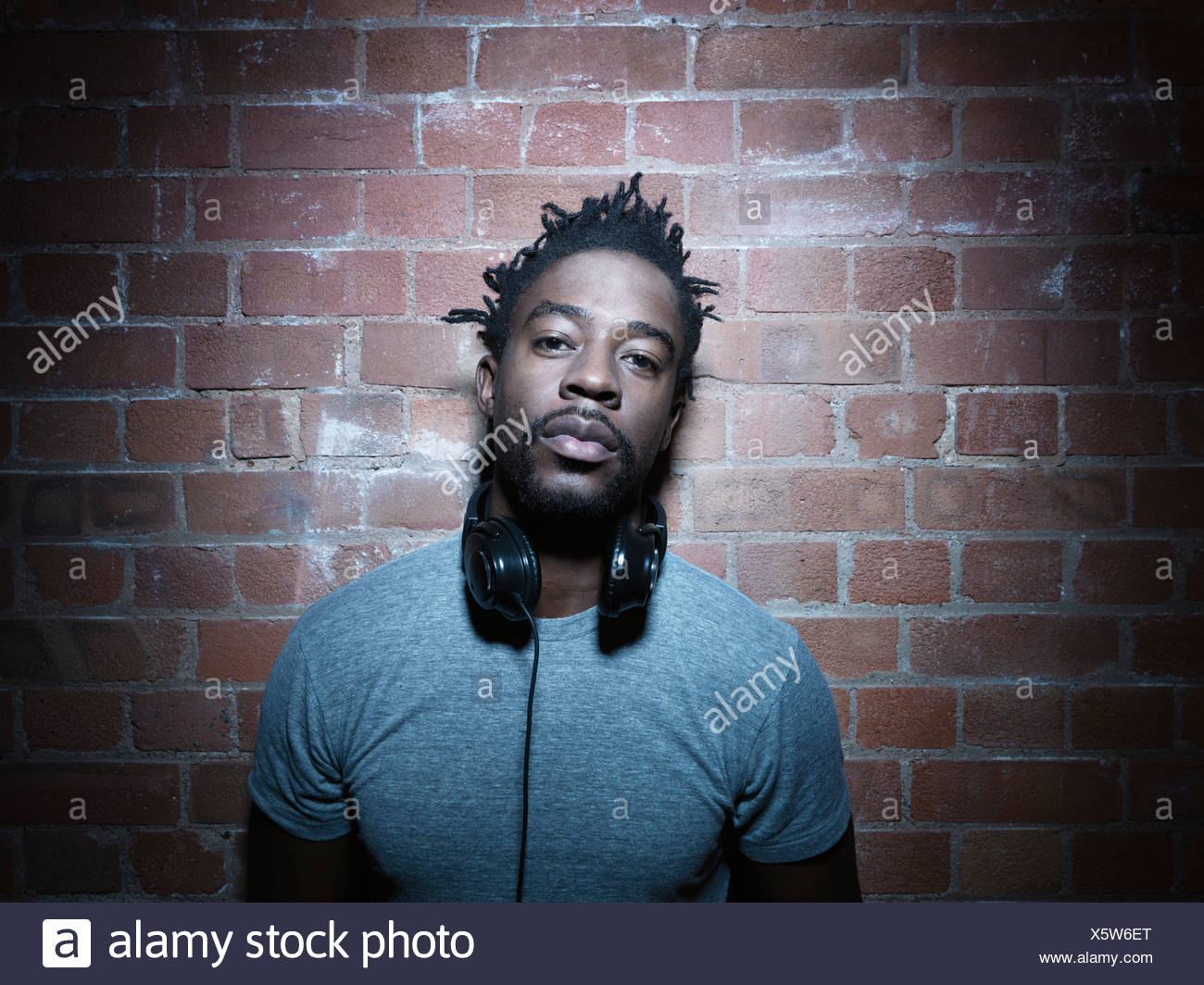 Man wearing headphones around neck - Stock Image