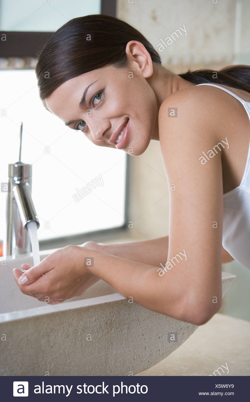 A woman washing at a sink - Stock Image