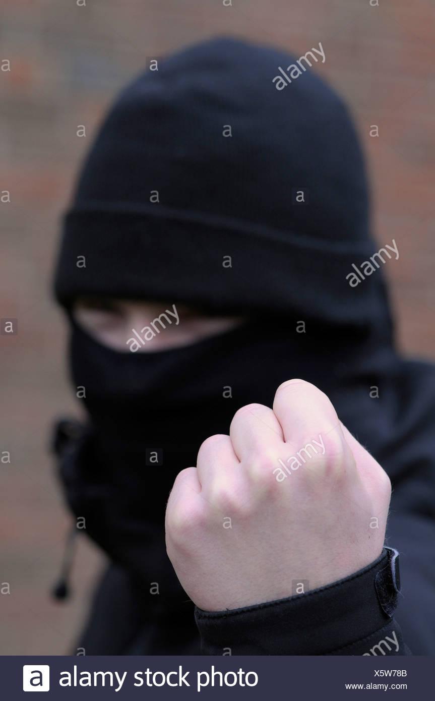 Youth holding balled fist toward camera - Stock Image