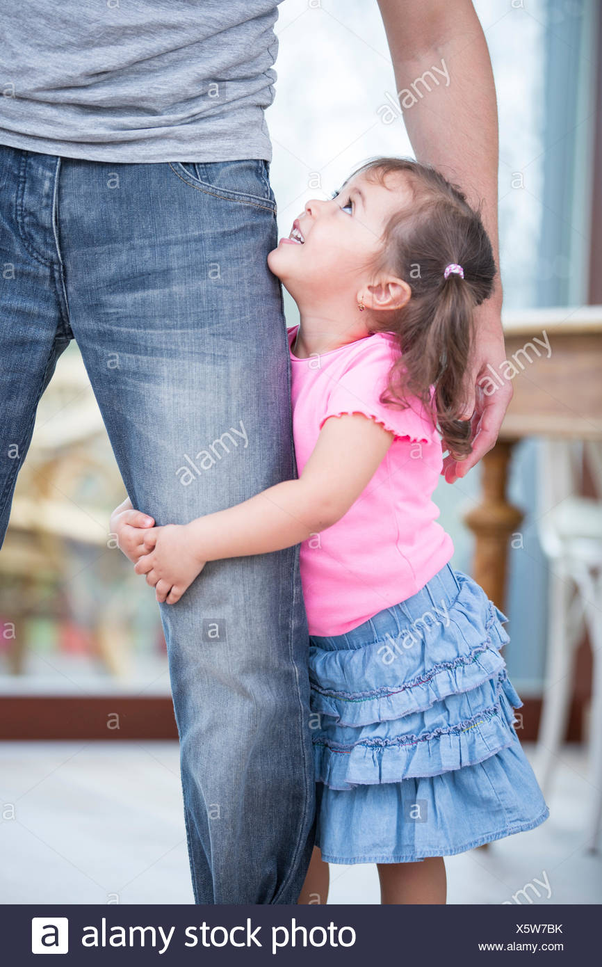 Side view of girl hugging father's leg in house - Stock Image