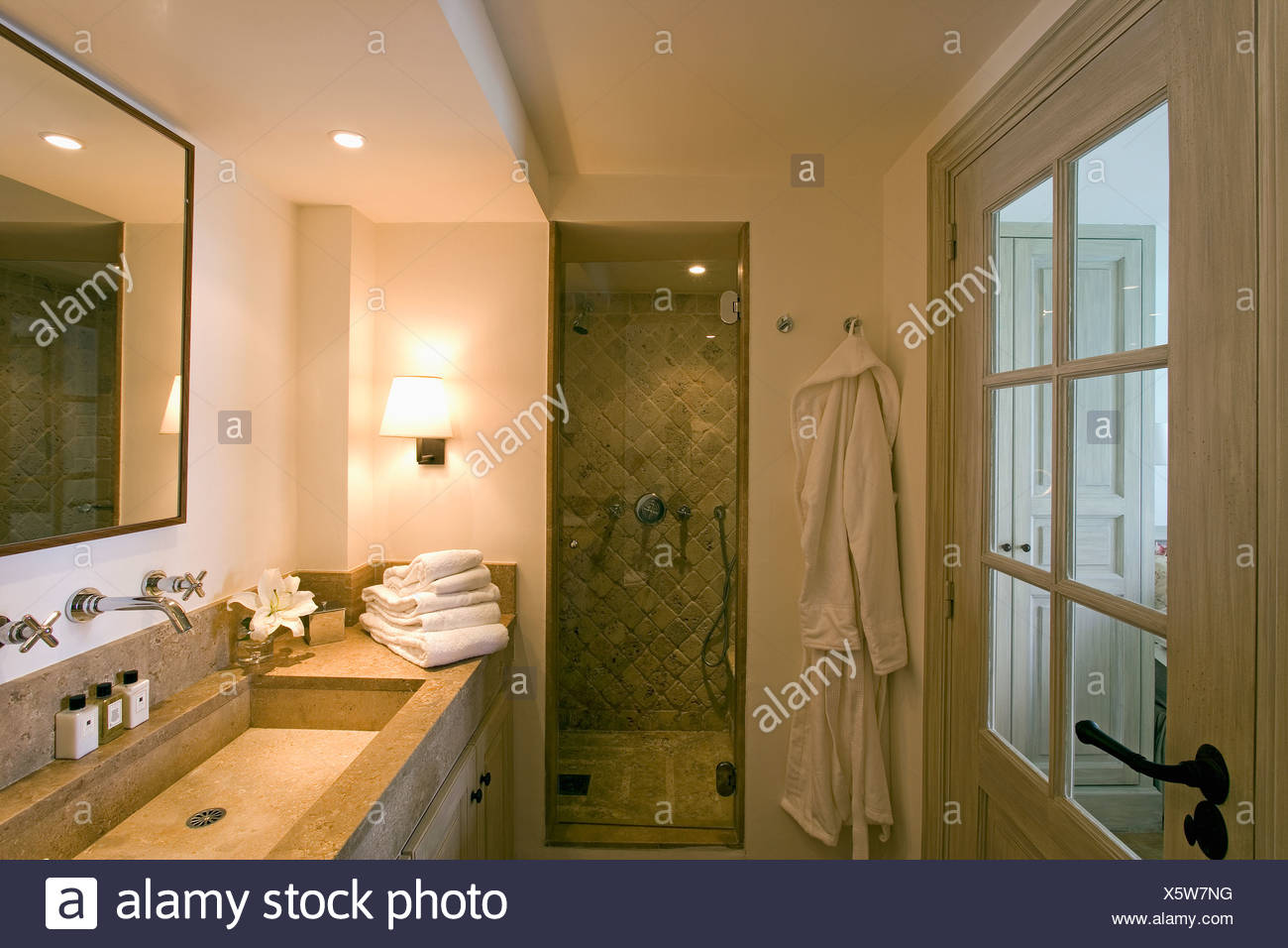 Rectangular stone basin in modern bathroom with bathrobe hanging ...