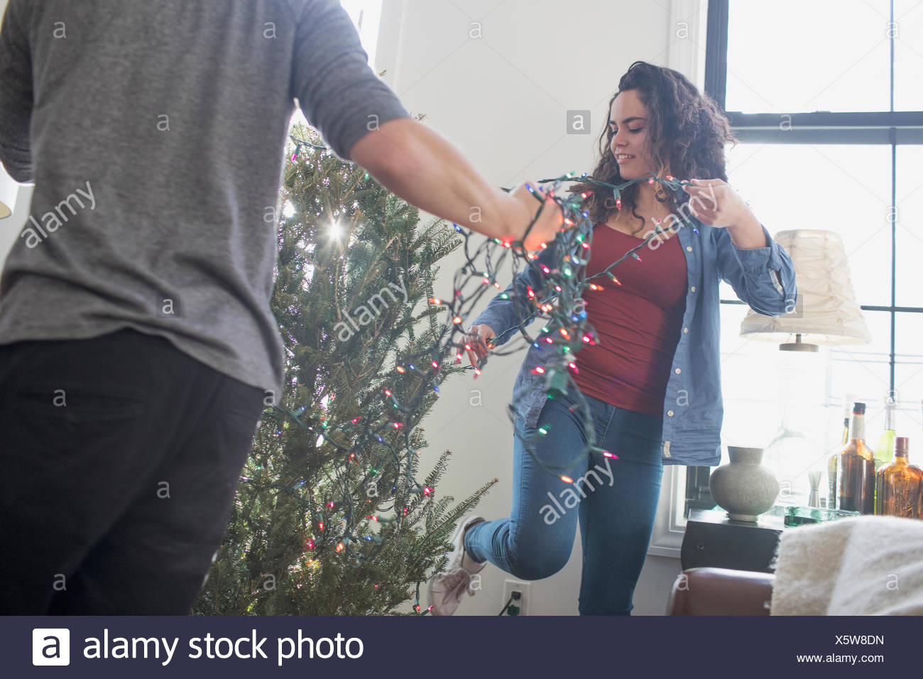 A young woman and man decorating a Christmas tree - Stock Image