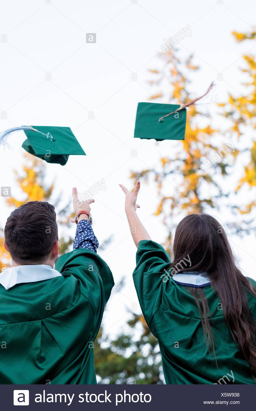Two college students throw their caps in the air during graduation ceremonies at a university in Oregon. - Stock Image