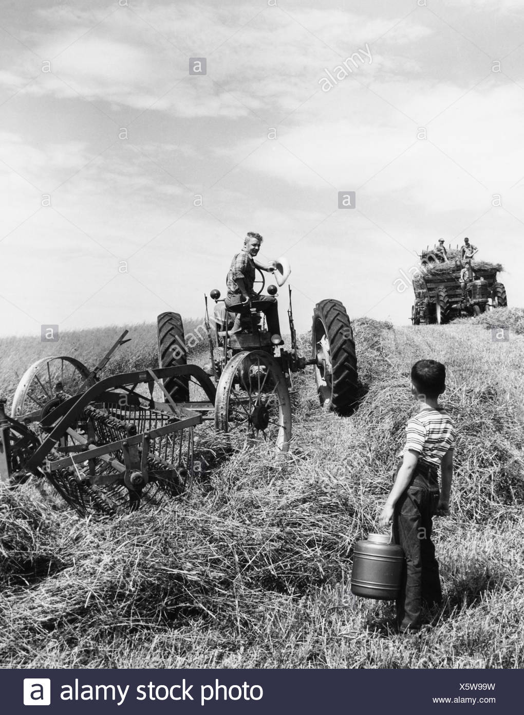 Young boy brings water to his father who is working the farm fields on a tractor - Stock Image