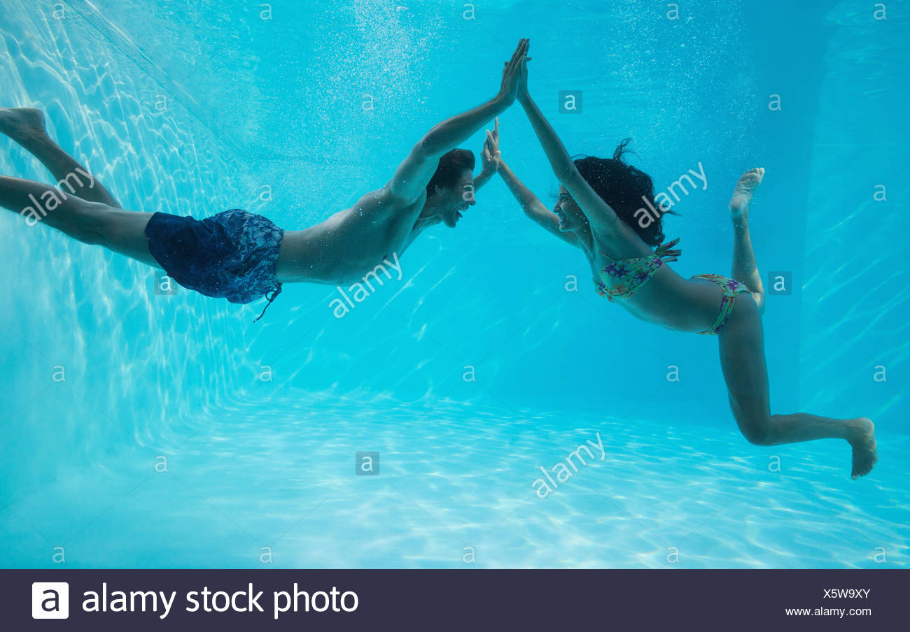 Couple holding hands and swimming underwater - Stock Image