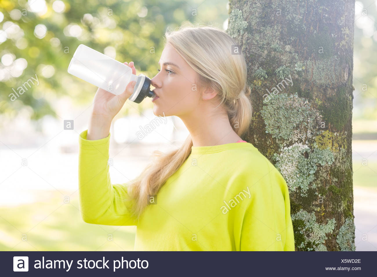 Fit peaceful blonde drinking from water bottle - Stock Image