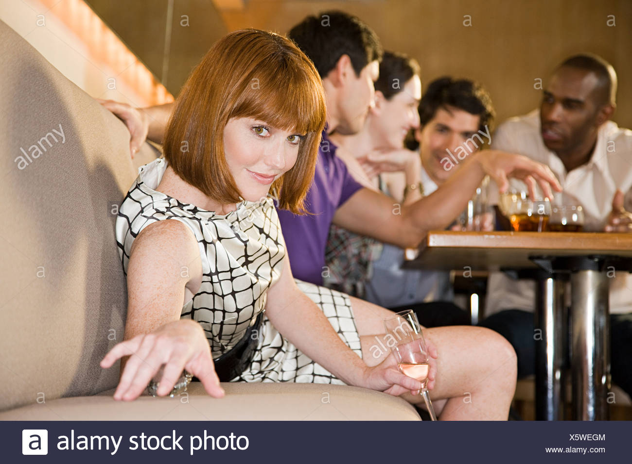 Young woman in a bar with friends - Stock Image