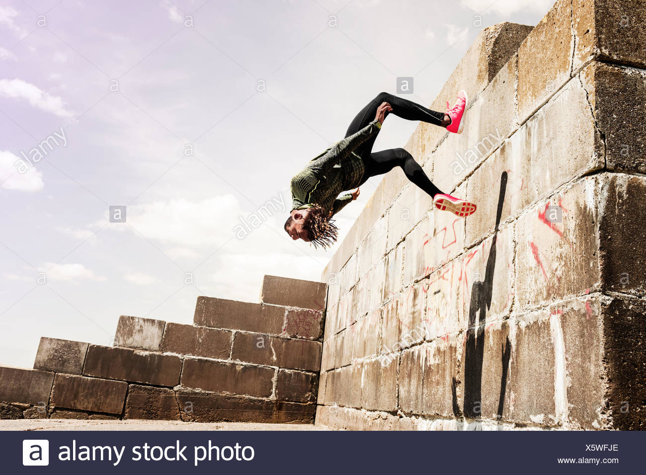 Young man, free running, outdoors, somersaulting from side of wall Stock Photo