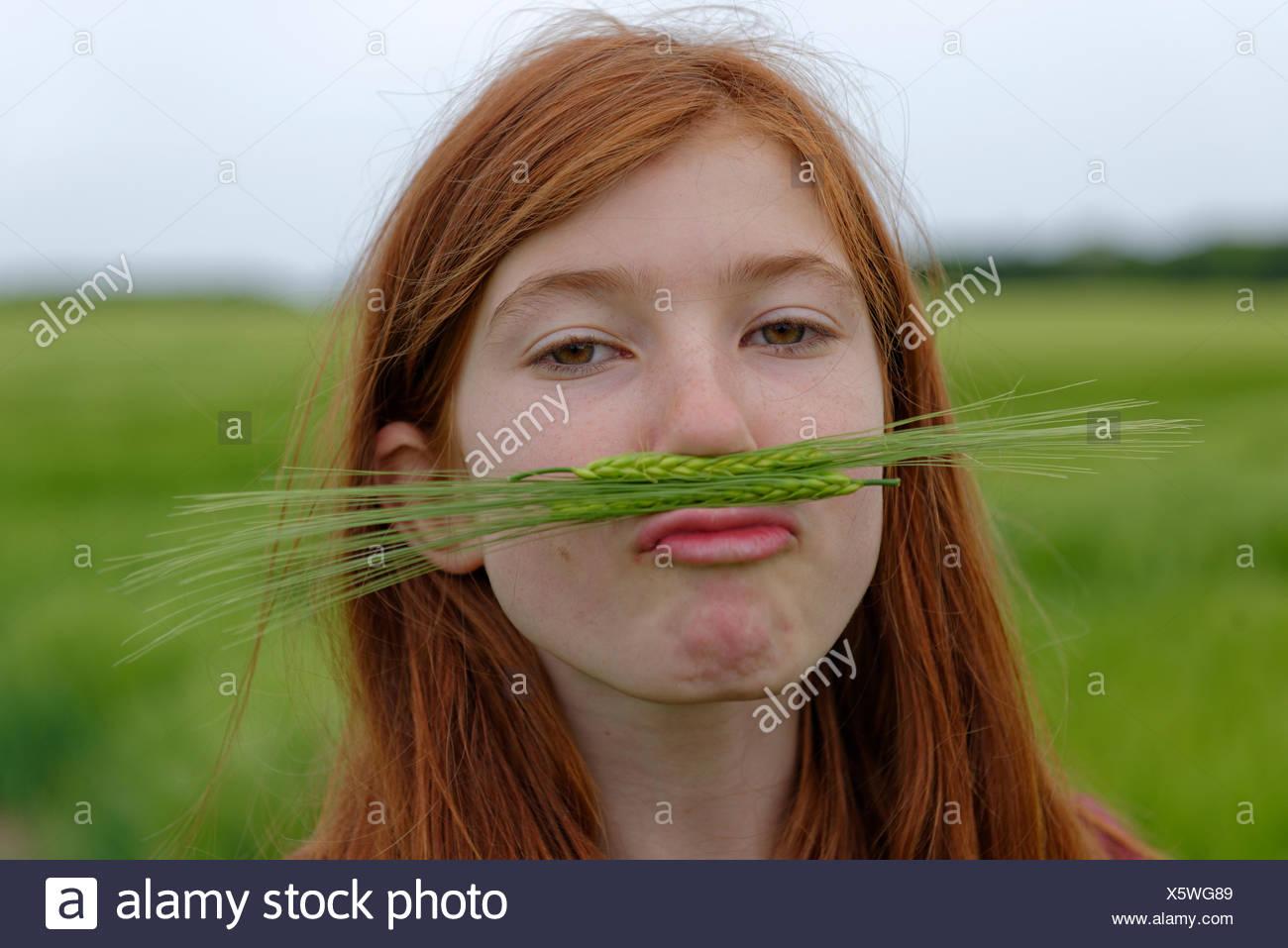 Portrait of teenage girl with barley moustache - Stock Image