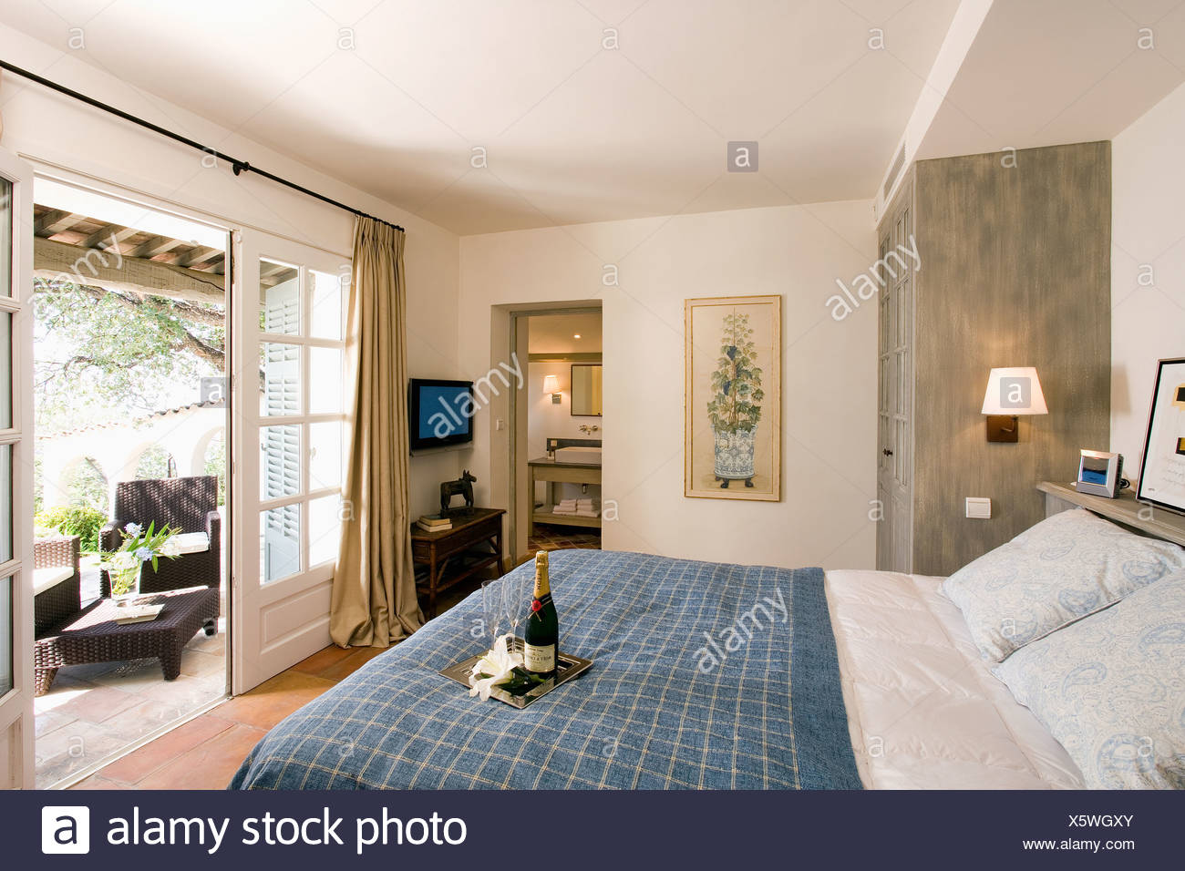 Open French doors with view of patio in modern bedroom in ...