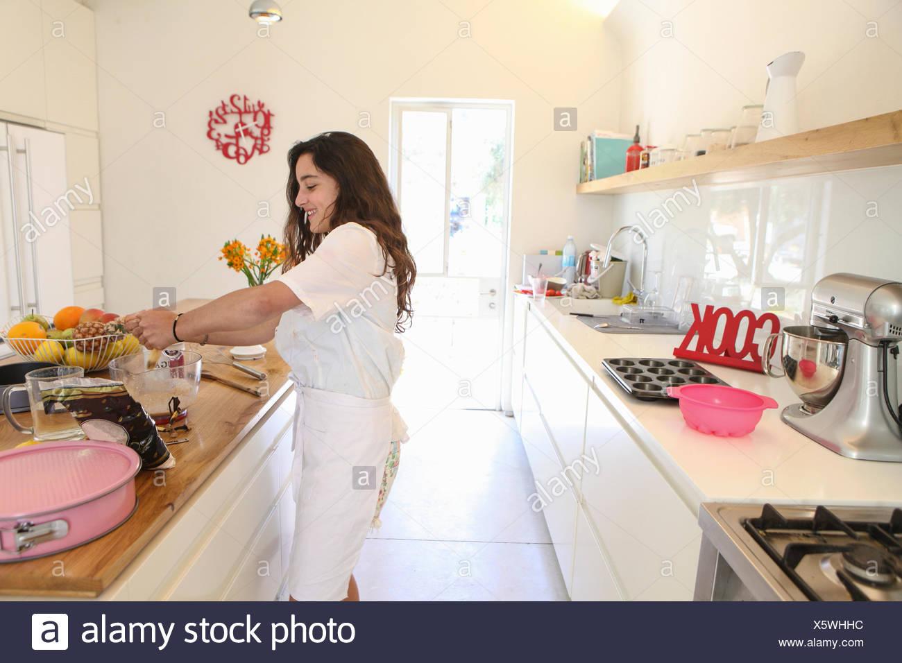 Teenage girl in white apron baking cake in kitchen - Stock Image