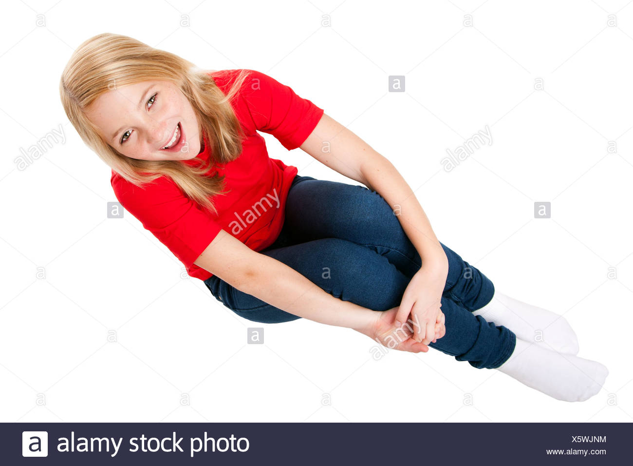 Beautiful cute teenager girl full of happiness sitting, isolated. - Stock Image