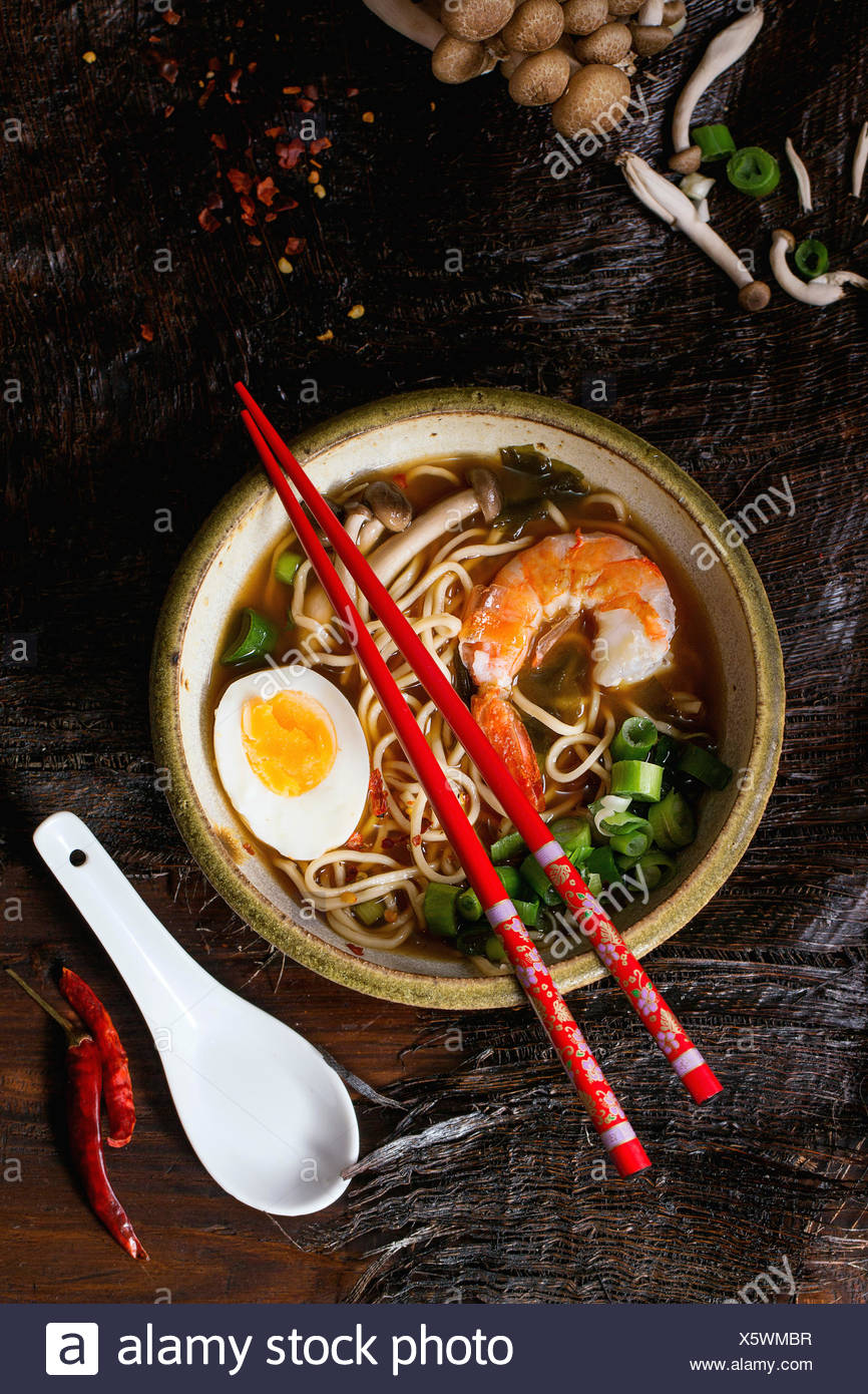 Ceramic bowl of asian ramen soup with shrimp, noodles, spring onion, sliced egg and mushrooms, served with red chopsticks and ch Stock Photo