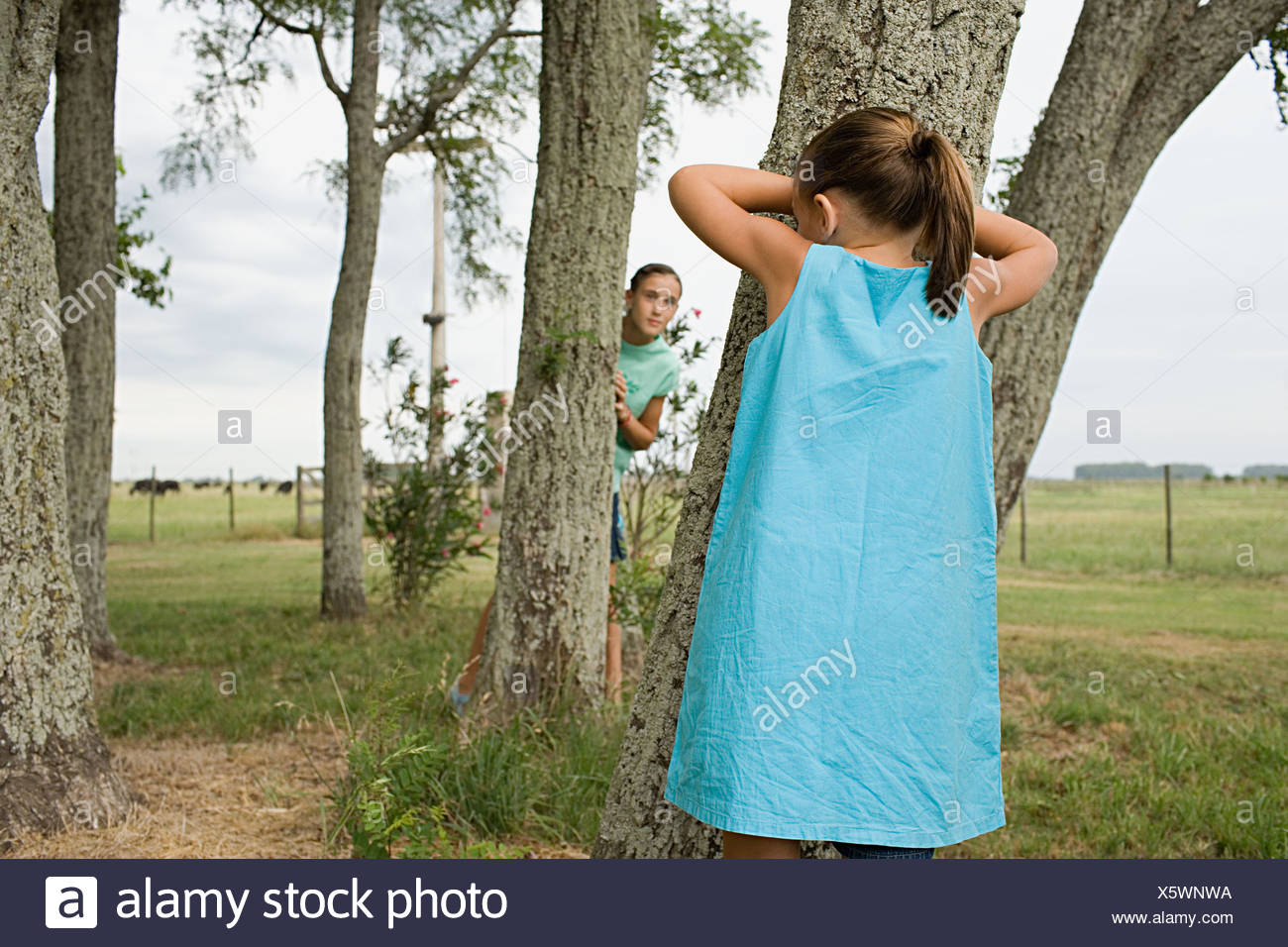 Girls playing hide and seek - Stock Image
