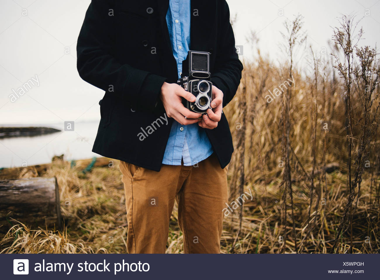 Midsection of man photographing through retro styled camera in park - Stock Image