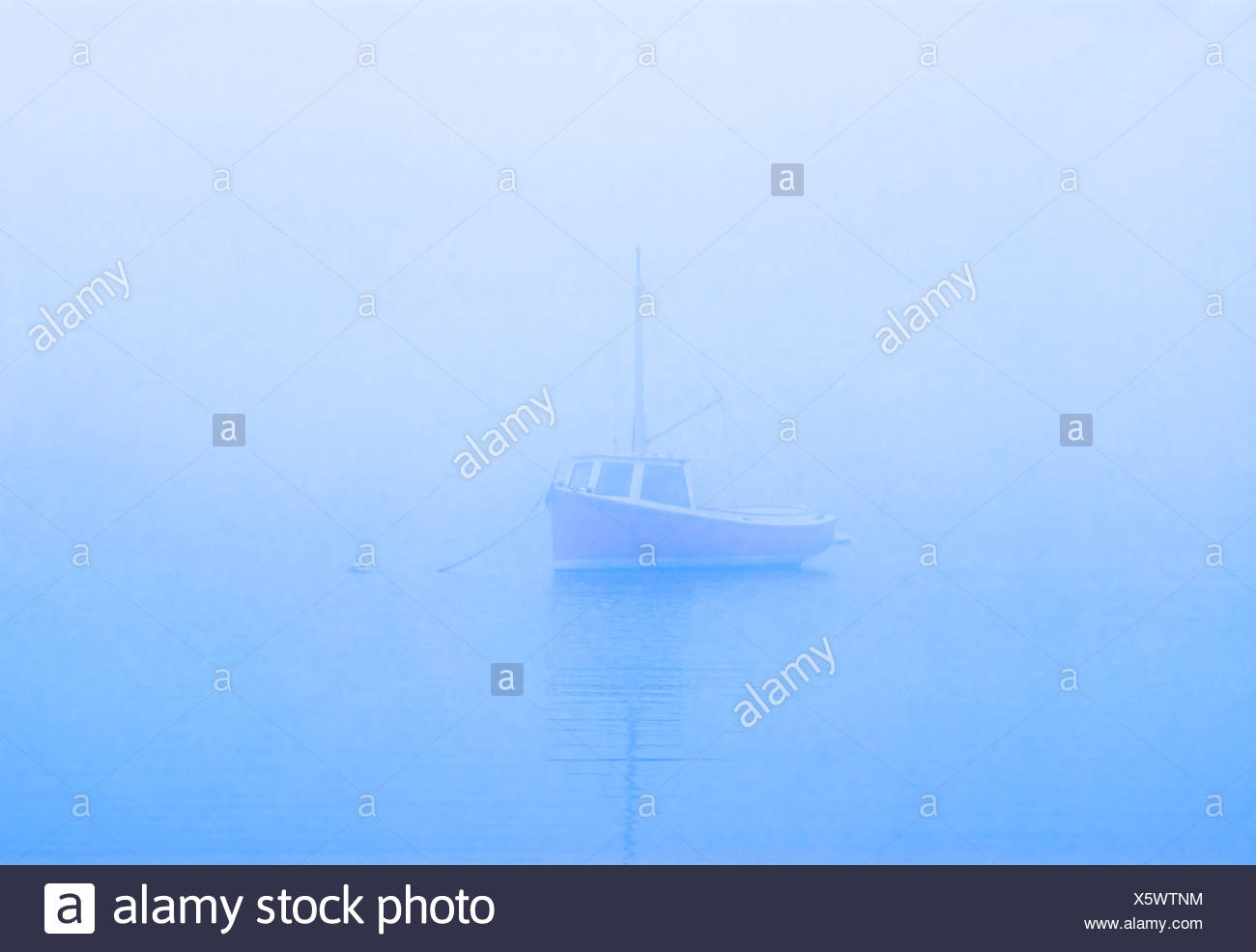 Lone boat on misty still water, Osterville, Cape Cod, MA - Stock Image