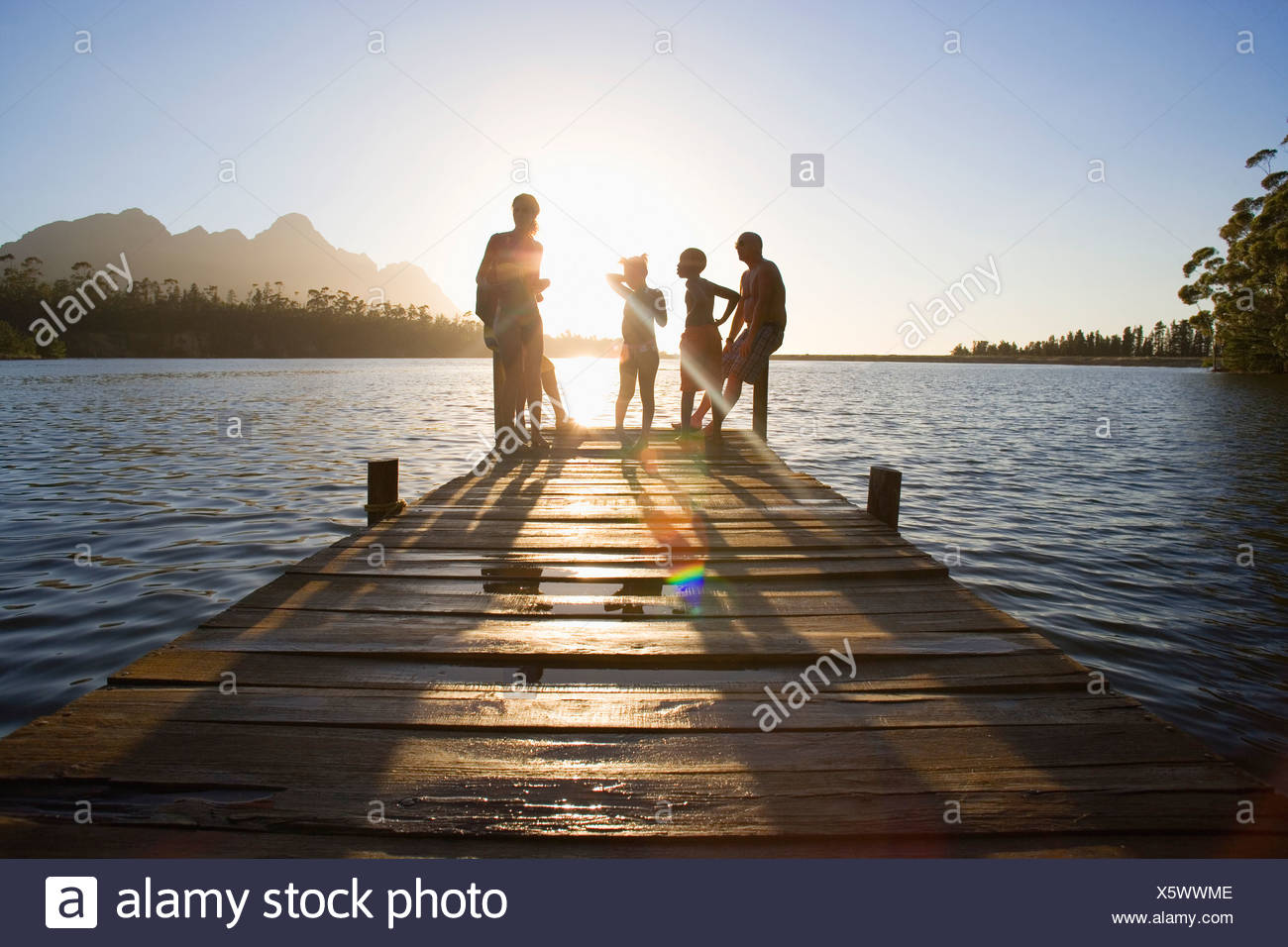 Family in swimwear standing at edge of lake jetty at sunset lens flare - Stock Image