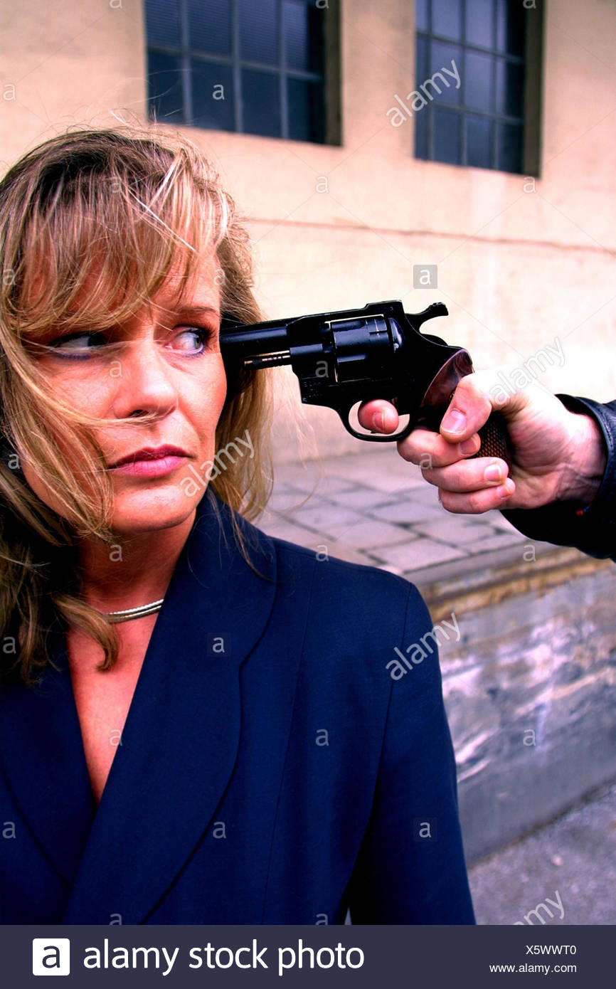 Man, woman, threat, revolver, readiness for violence criminal activity, criminal, criminal, power, weapon, threaten, threat, danger, aggression, attack, threat, raid, violent criminal, criminal offence, brutality, raid, attacked, threaten, outside - Stock Image