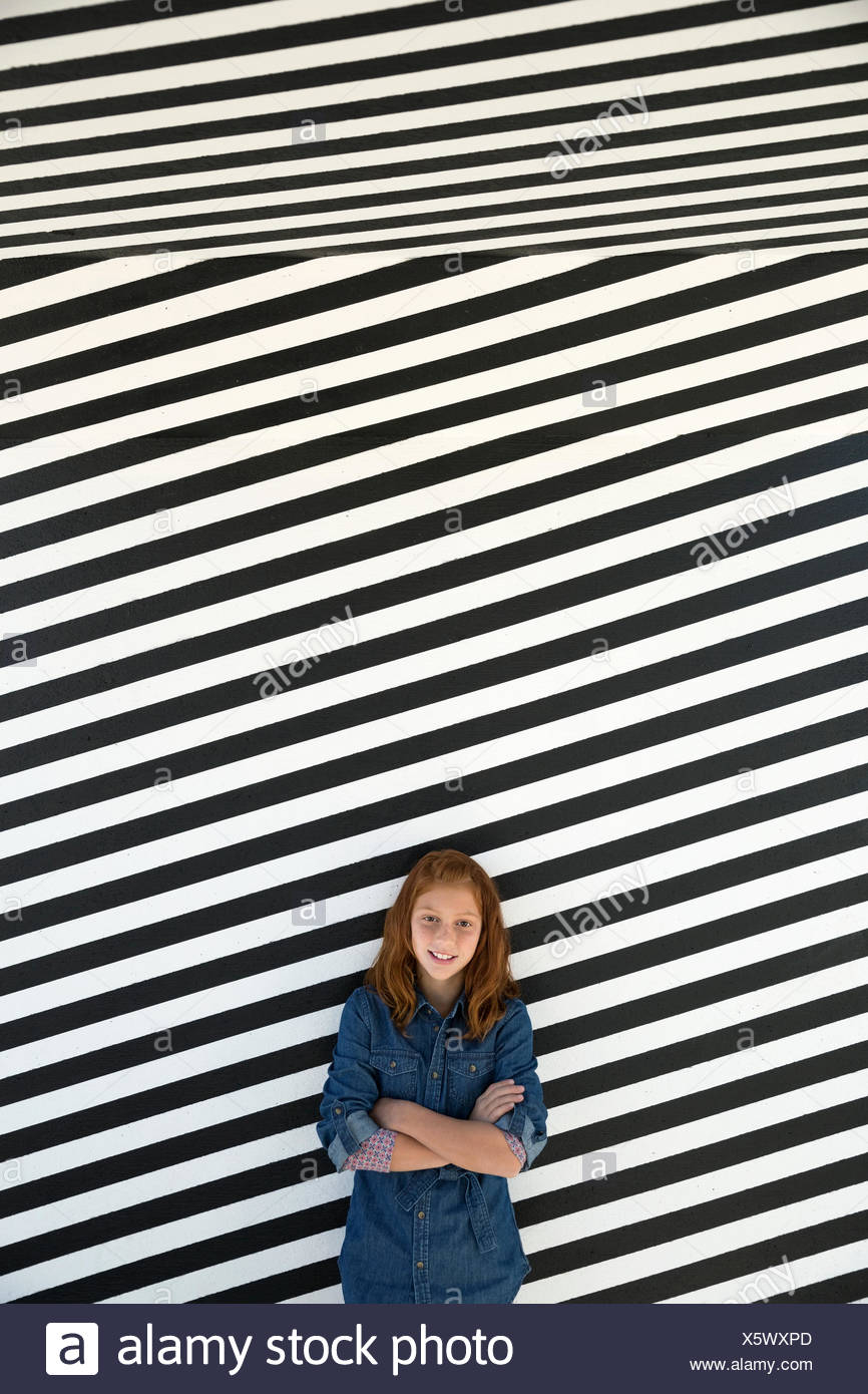 Portrait girl against black and white striped wall - Stock Image