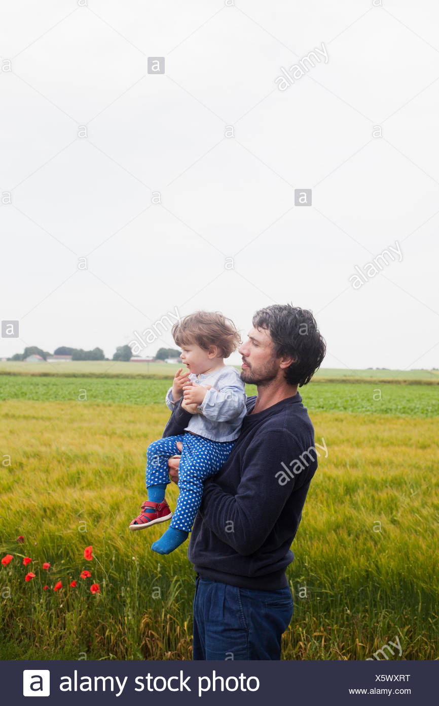 Sweden, Skane, Osterlen, Dad standing in fields and carrying daughter (2-3) - Stock Image