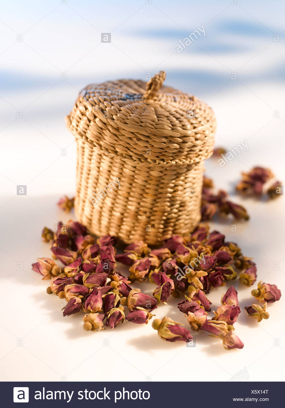 Bast basket and dried rose petals - Stock Image
