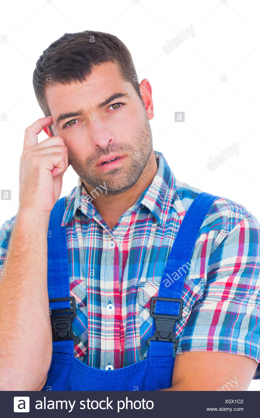 Portrait of confused manual worker scratching head - Stock Image